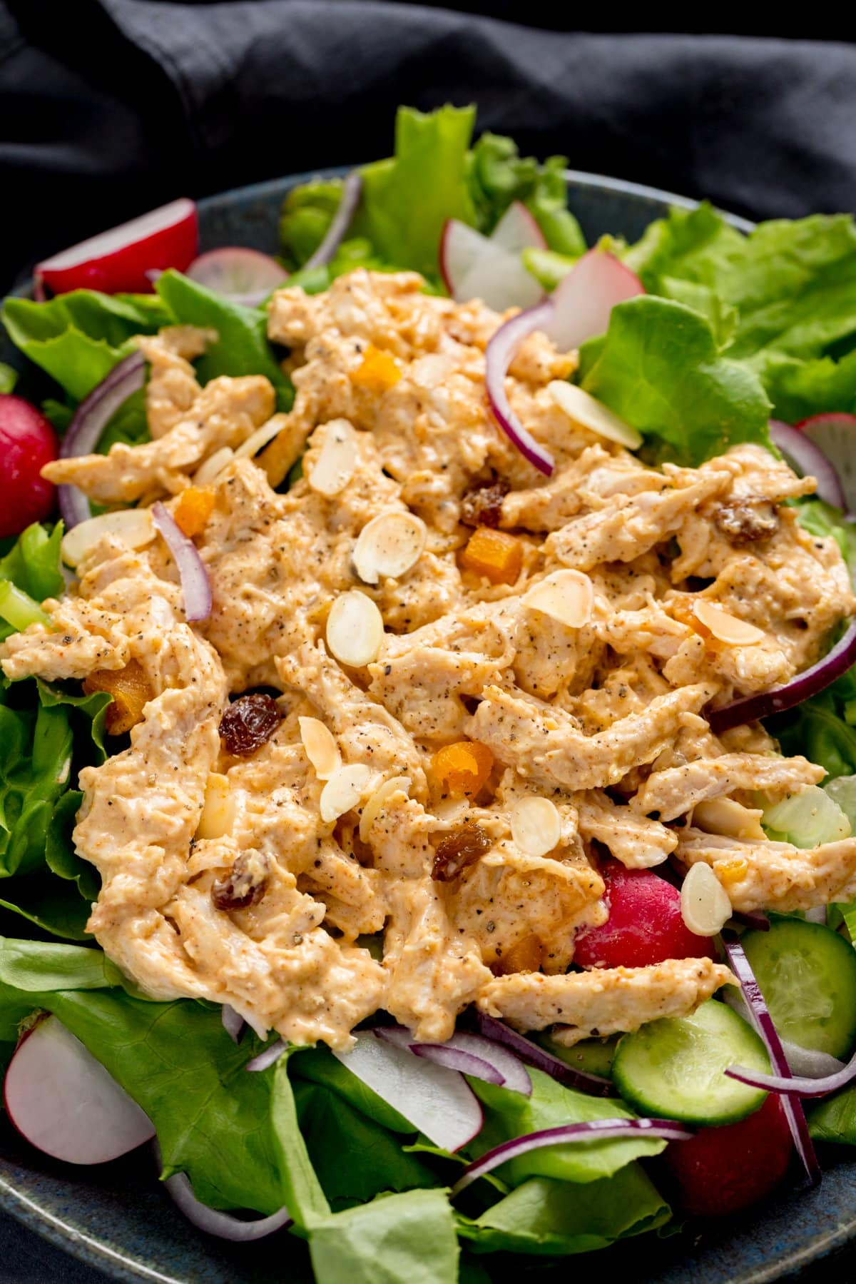 Overhead of coronation chicken on a bed of salad on a dark surface.