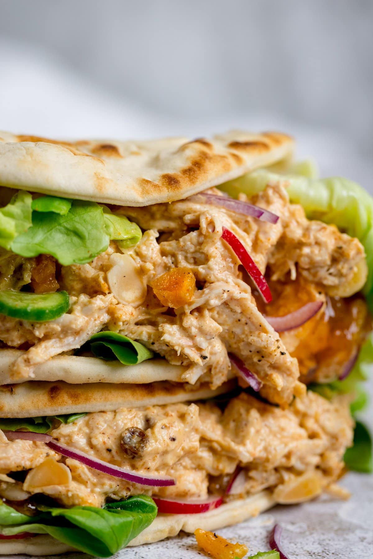 Close up image of coronation chicken and salad on a folded flatbread, stacked on another flatbread, against a light background.