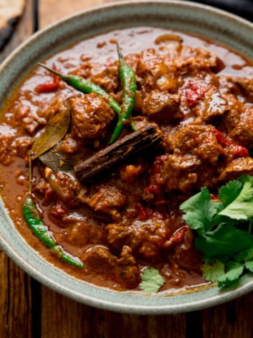 Lamb Bhuna curry in a green bowl on a wooden table