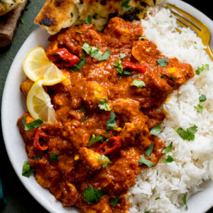 chicken pathia and boiled rice on a white plate. Curry is topped with lemon slices and coriander.