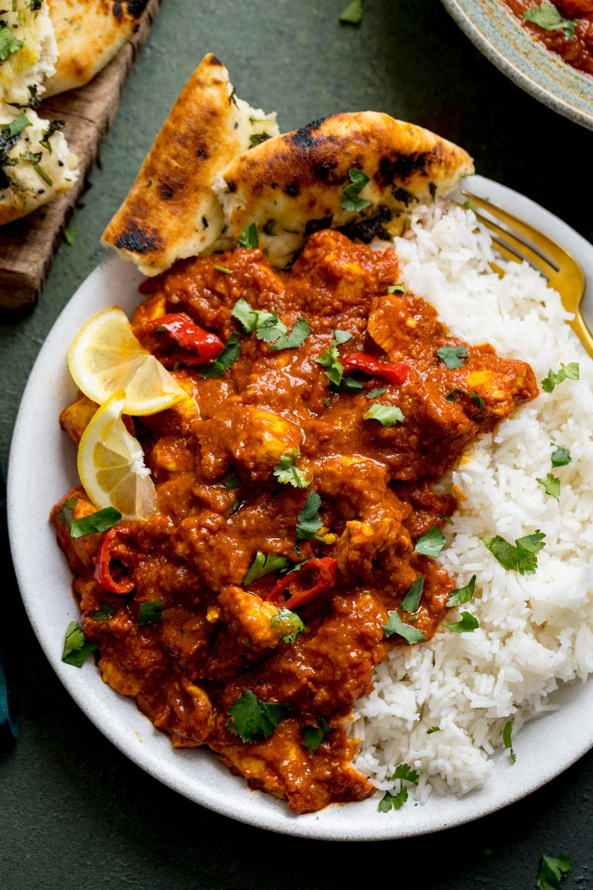 Chicken pathia with boiled rice and lemon slice son a white plate with naan bread. Plate is on a dark background,