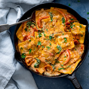 Overhead shot of ravioli in creamy tomato sauce in a black pan on a blue surface. There is a spoon in the pan and a light blue napkin next to the pan.