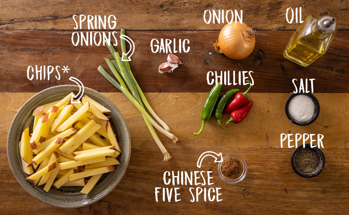 Labelled ingredients for making salt and pepper chips on a wooden board.
