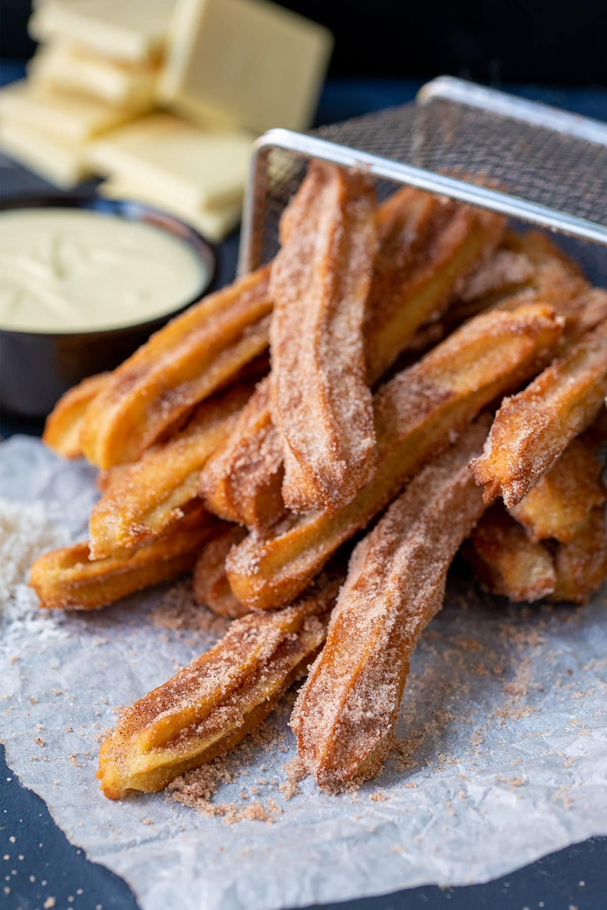 Picture of baked churros dusted with cinnamon sugar on their side in a wire basket with white chocolate in the background out of focus.