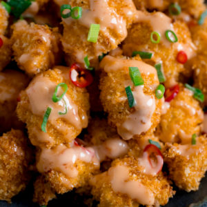 Close up of Crispy Cauliflower with bang bang sauce topped with chillies and spring onions