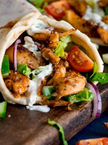 side shot of chicken gyros rolled up in a flatbread with lettuce, tomato, red onion and tzatziki. The gyros is on a dark wooden board with further ingredients scattered around.