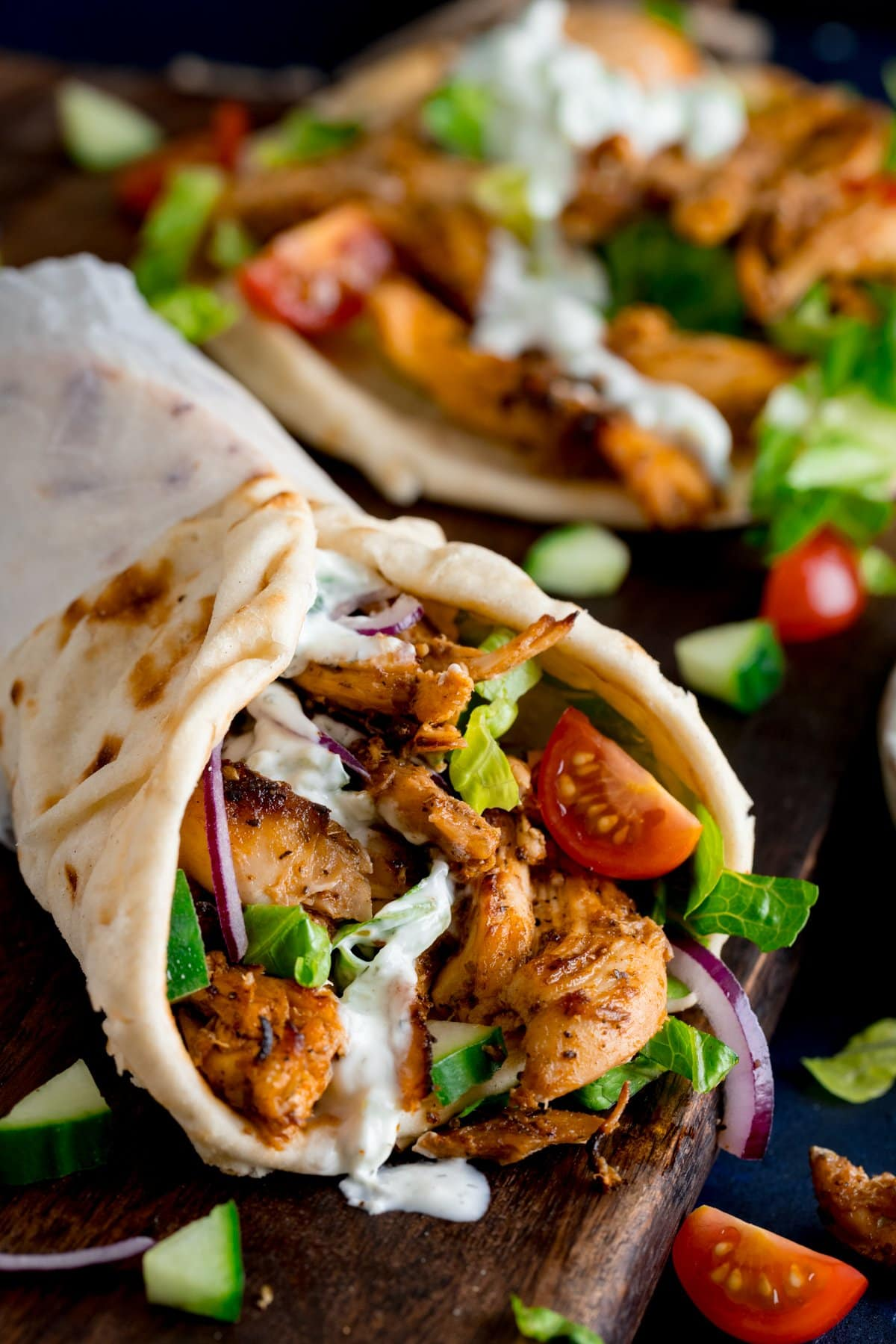 Chicken gyros in a rolled up flatbread with tzatziki and salad on a wooden board. Further ingredients and an unrolled gyros flatbread (with toppings) also in shot.