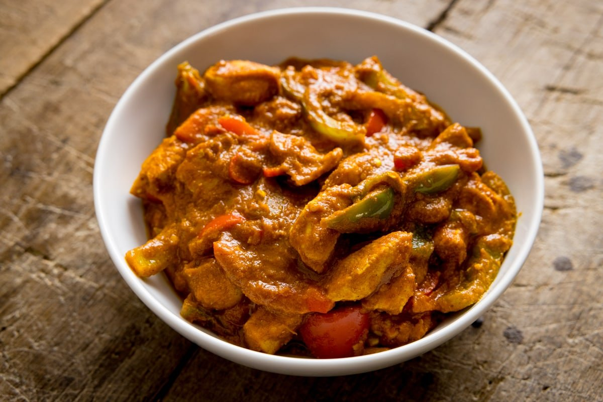 White bowl filled with chicken jalfrezi that has been made using curry base gravy. Bowl is on a wooden table.