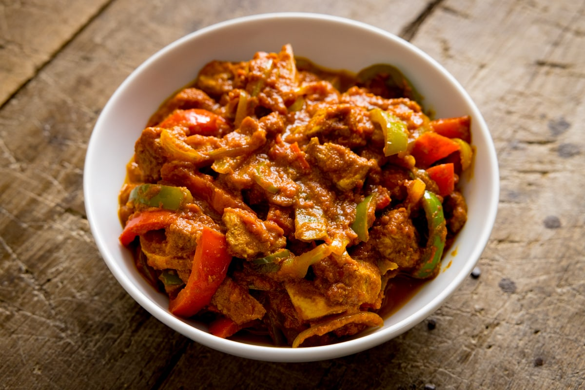 White bowl filled with chicken jalfrezi on a wooden table.