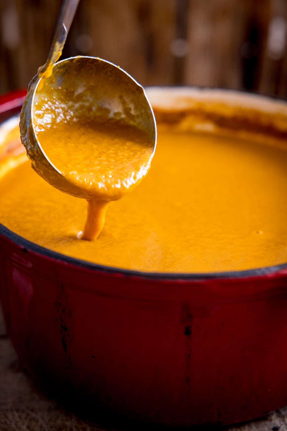 Ladle of curry base gravy being poured into a red cast iron pan.