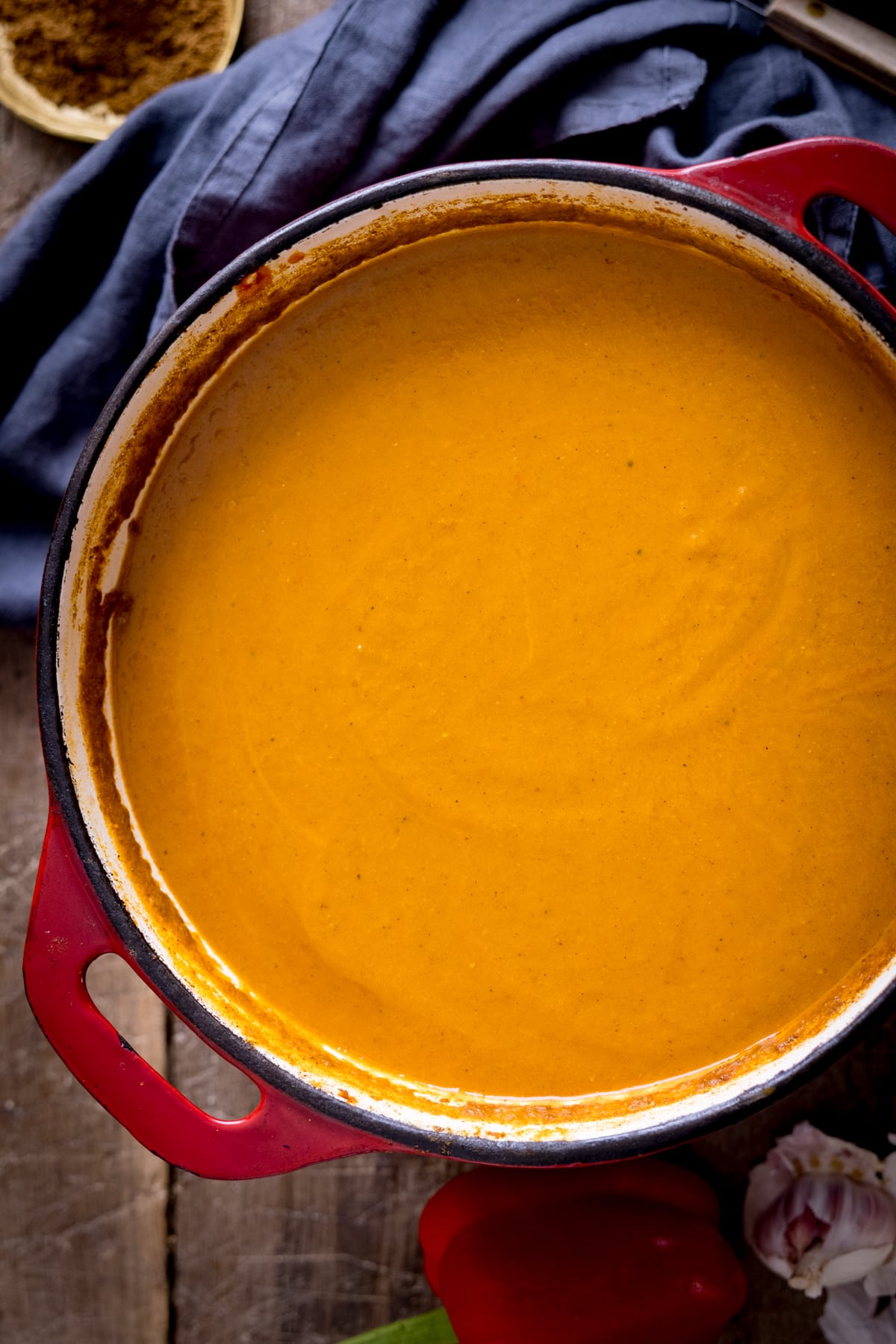 Overhead of curry base gravy in a red cast iron pan next to a blue napkin.