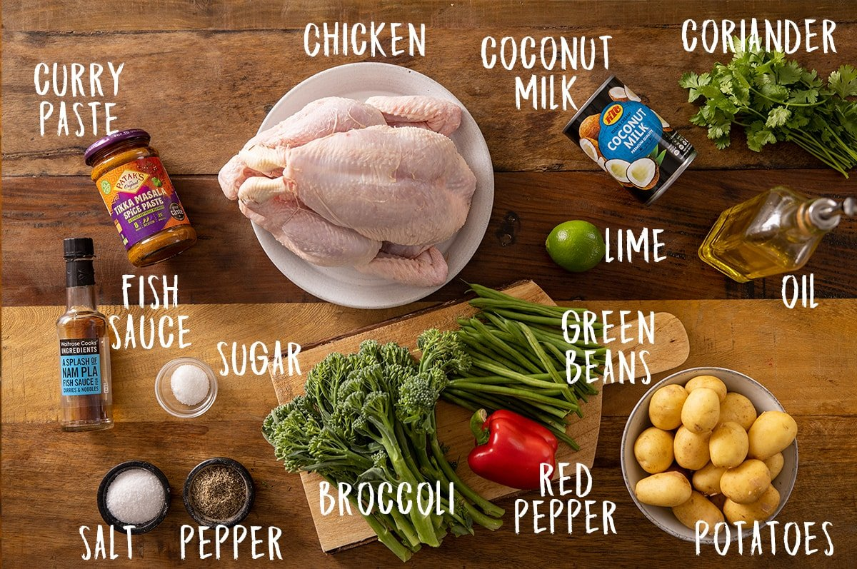 Ingredients for curry roast chicken on a wooden table.