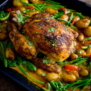 Curry roast chicken in a baking tin with potatoes, vegetables and curry sauce.