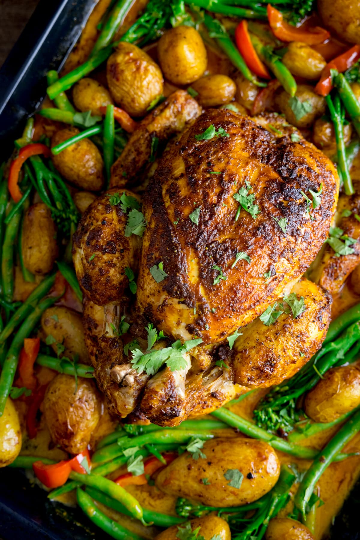 Overhead of a whole roast chicken in a baking tray with potatoes, peppers, green beans, broccoli and curry sauce