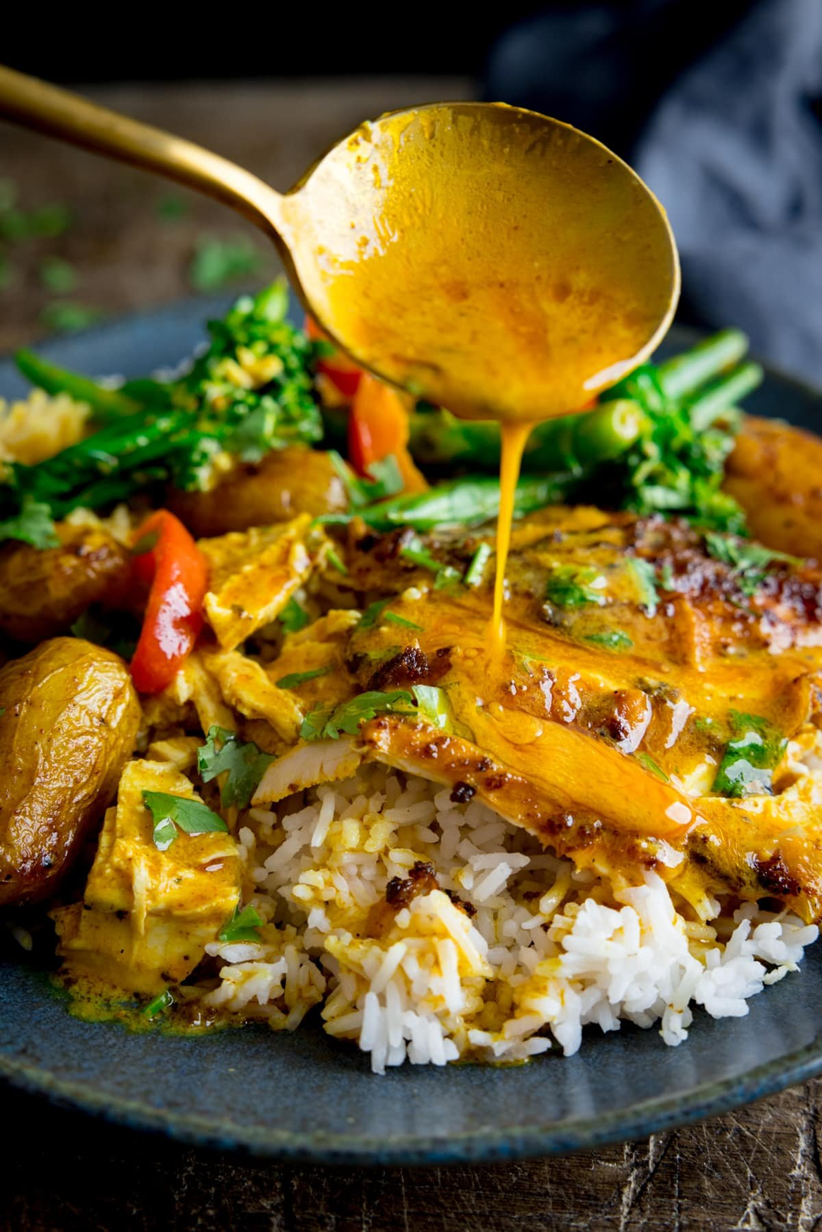 Curry sauce being spooned onto slices of curry roast chicken which is on a plate with rice and vegetables.