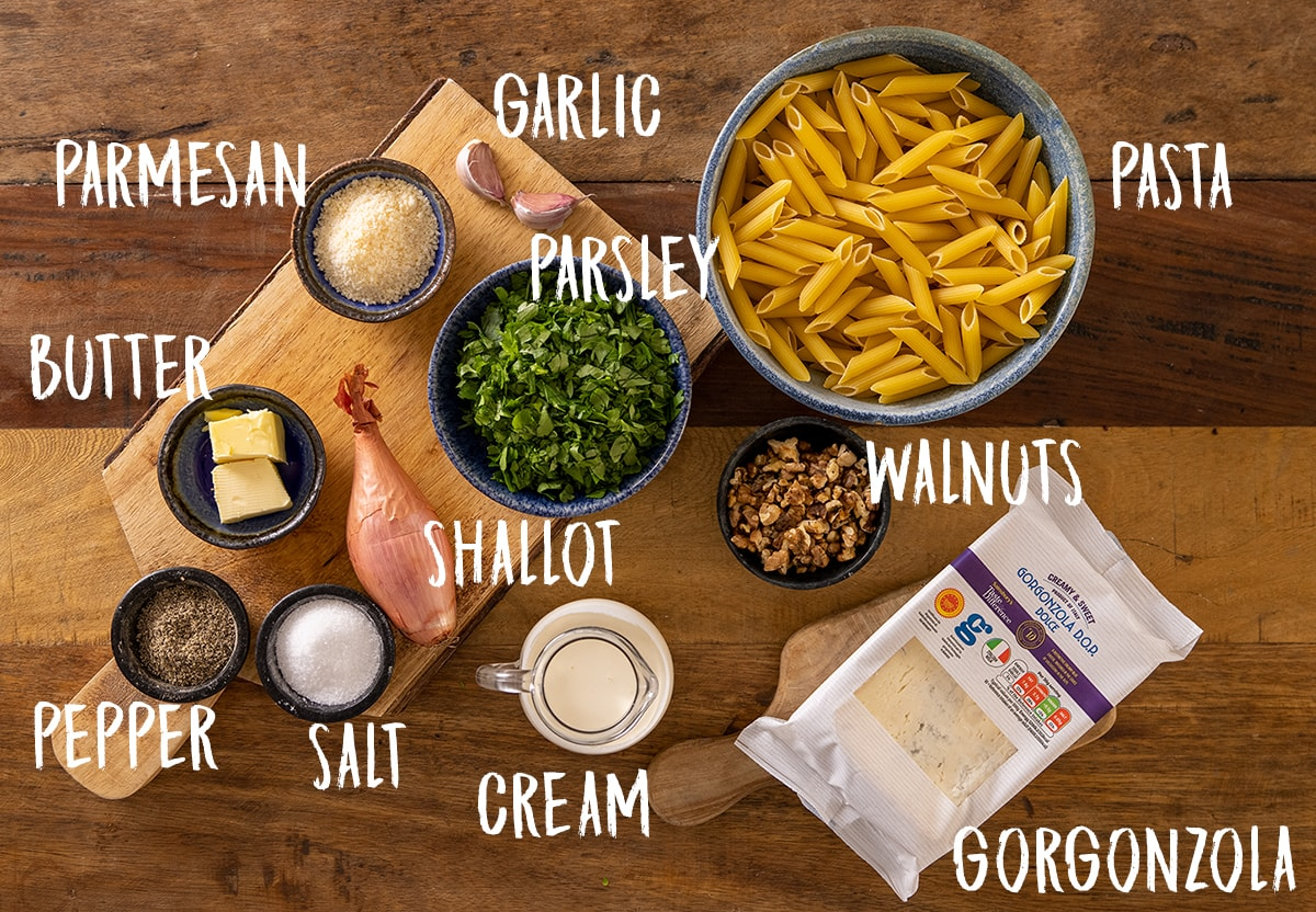 Labelled ingredients for making gorgonzola pasta on a wooden board.
