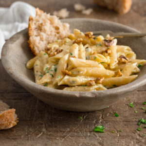 Square image of gorgonzola pasta in a light grey bowl on a wooden table. There is a piece of torn bread in the bowl with the pasta.