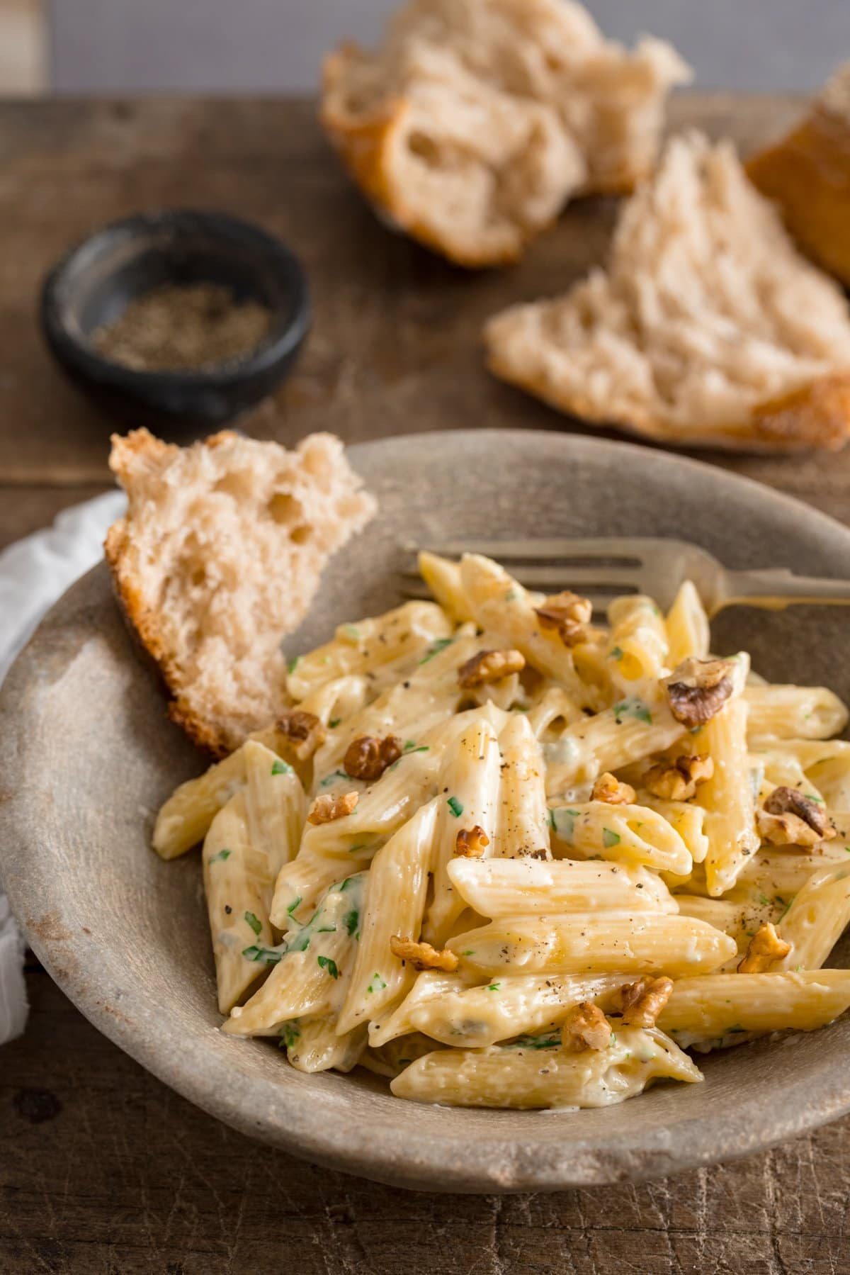 Gorgonzola pasta in a stone bowl on a wooden table. Pieces of bread in the bowl and in the background.