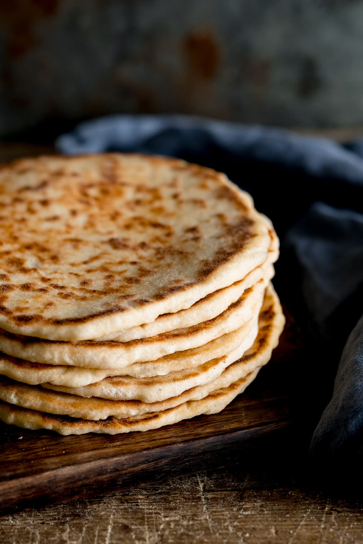 A stack of flatbreads on a wooden board against a dark background, next to a blue napkin.
