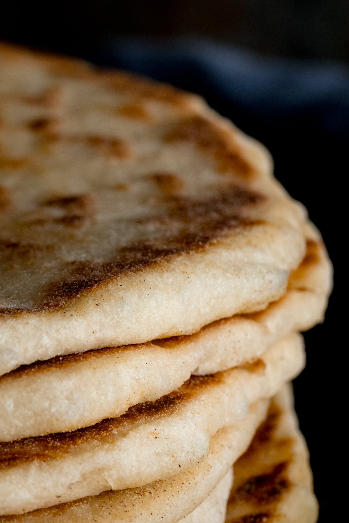 Close up of the edge of a stack of flatbreads, against a dark background.