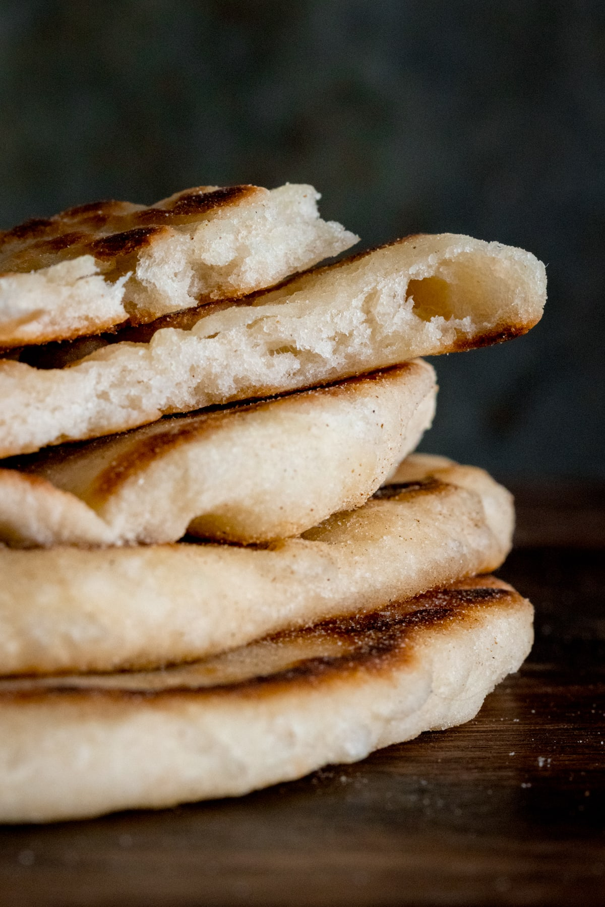Close up a stack of flatbreads against a dark surface