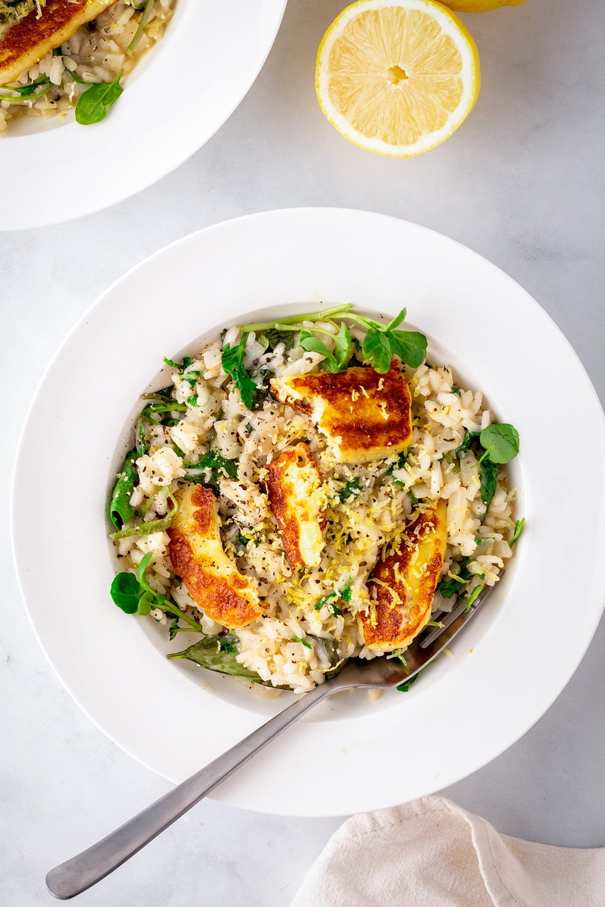 A white bowl with cooked lemon risotto topped with pieces of fried halloumi and a slice of lemon in the background.