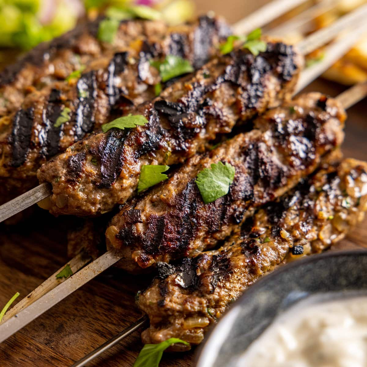 Close up pictures of lamb koftas on metal skewers sat on a wooden board with a bowl of dipping sauce in the foreground out of focus.
