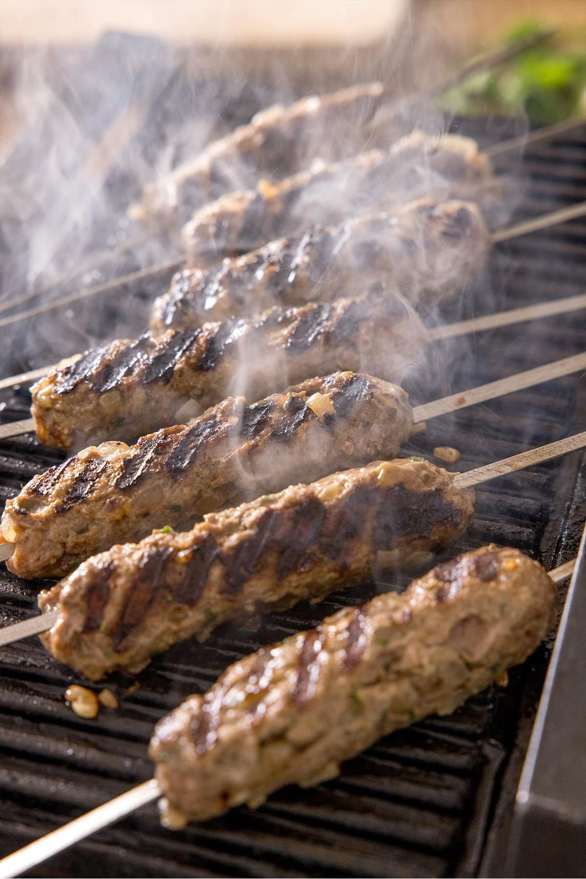 Lamb koftas being cooked on a griddle with steam rising.