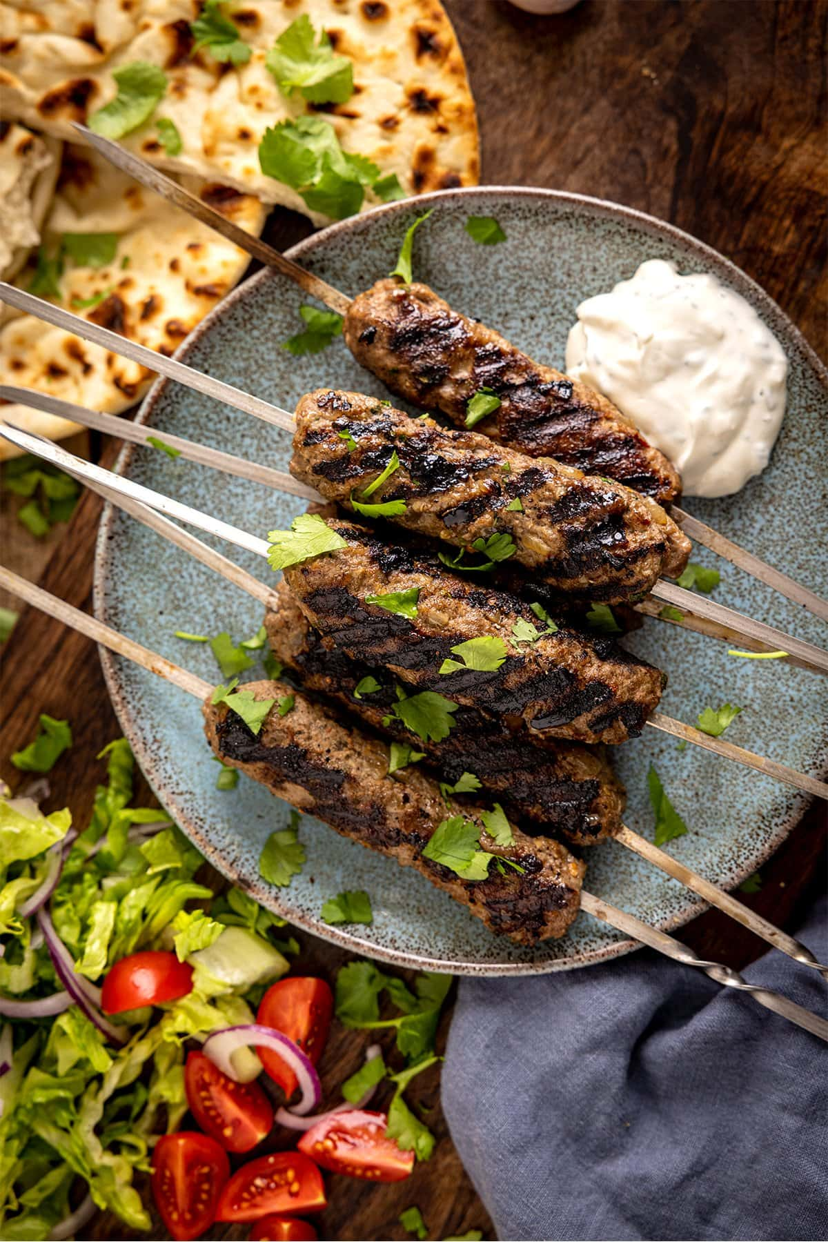 Overhead picture of Lamb Kofta Kebabs pilled up on a plate with some flatbreads and salad in the background.