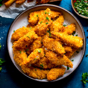 Overhead photo of a bowl full of crispy baked chicken goujons on a blue background.