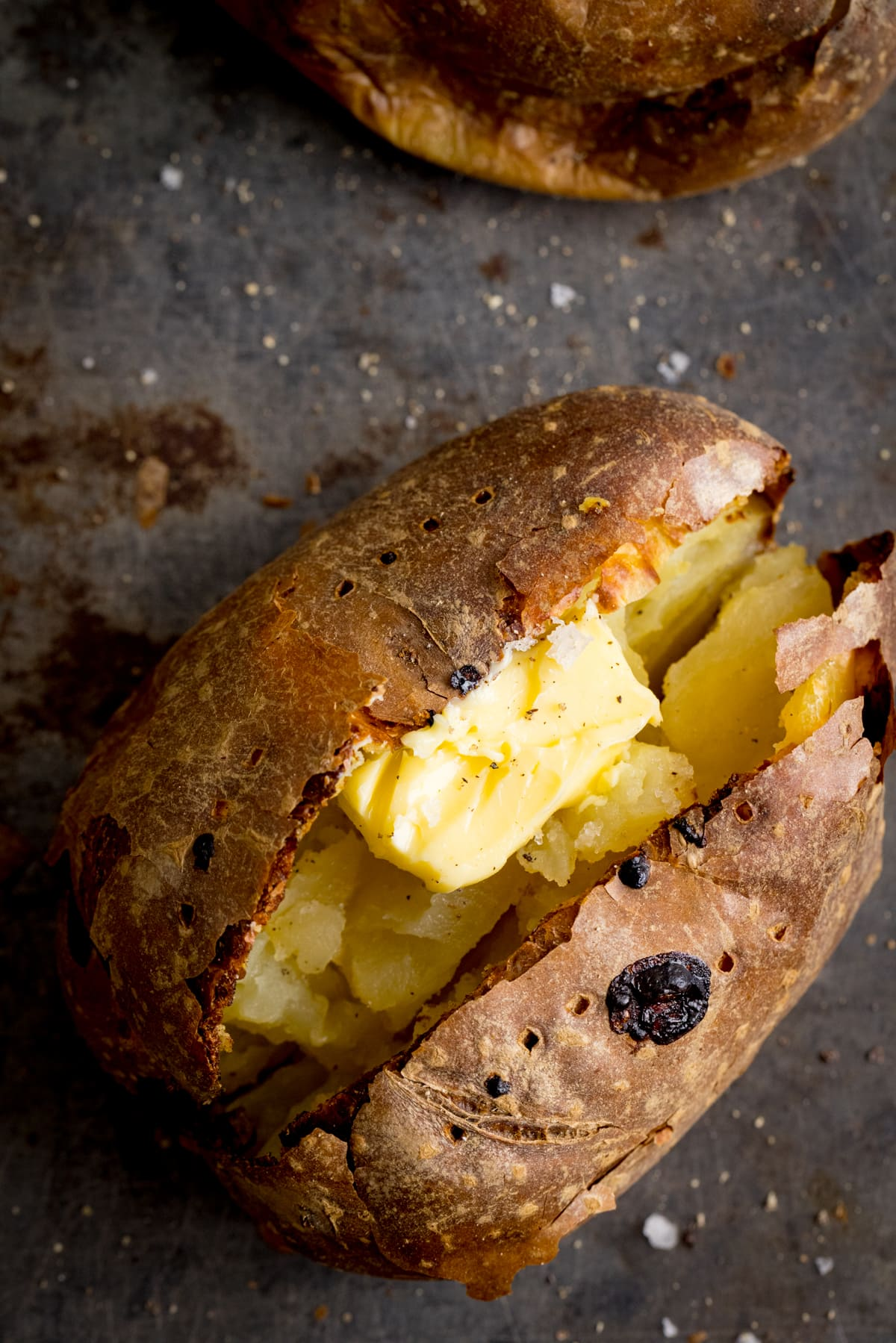 Overhead image of an open baked potato on a dark metal background. Potato was baked using method 2 of my baked potato experiment.