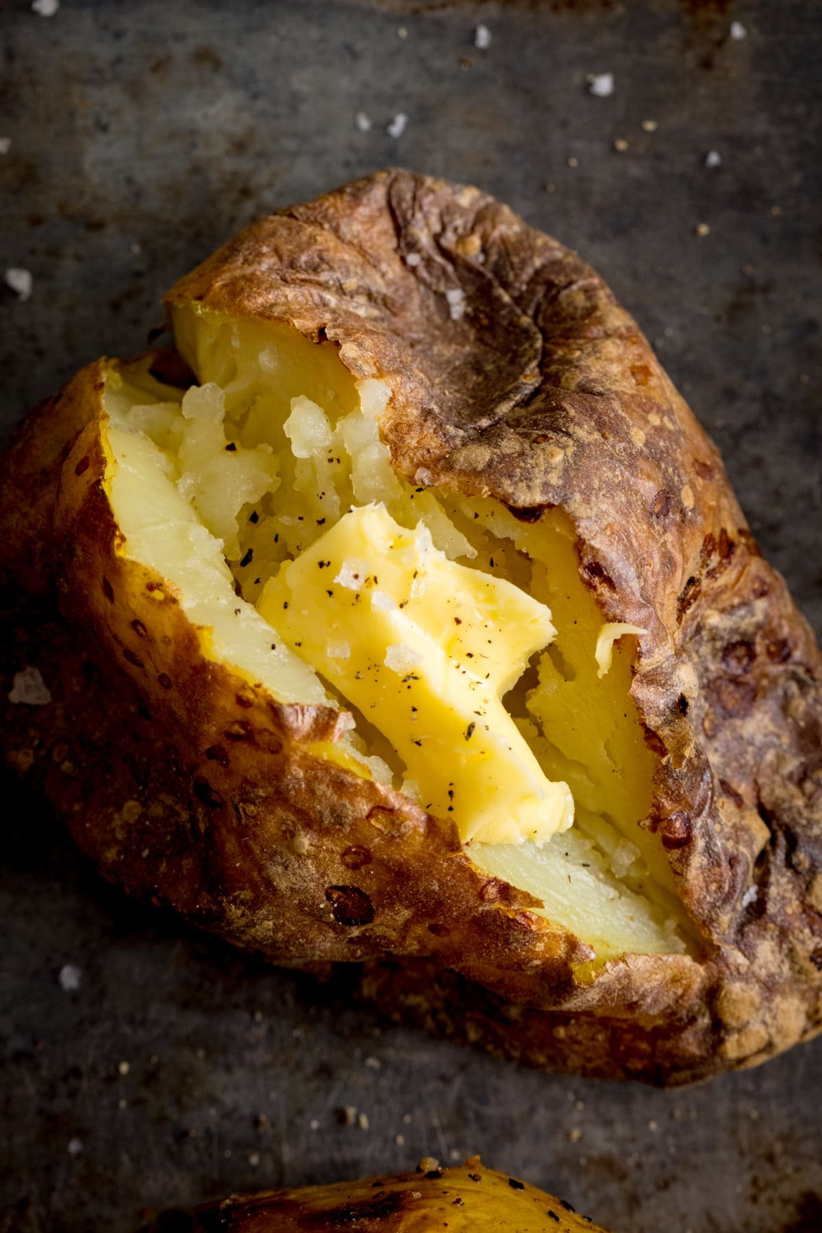 Overhead image of an open baked potato on a dark metal background. Potato was baked using method 7 of my baked potato experiment.