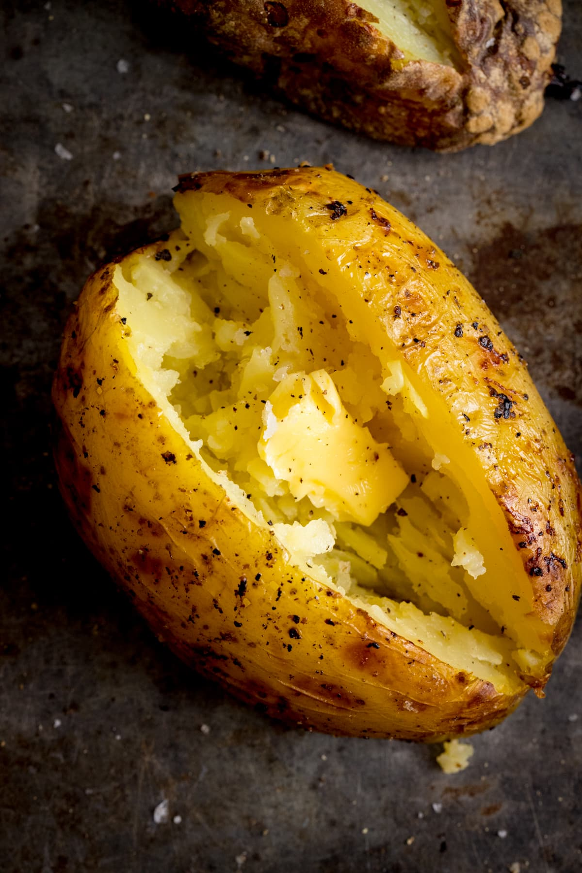 Overhead image of an open baked potato on a dark metal background. Potato was baked using method 8 of my baked potato experiment.