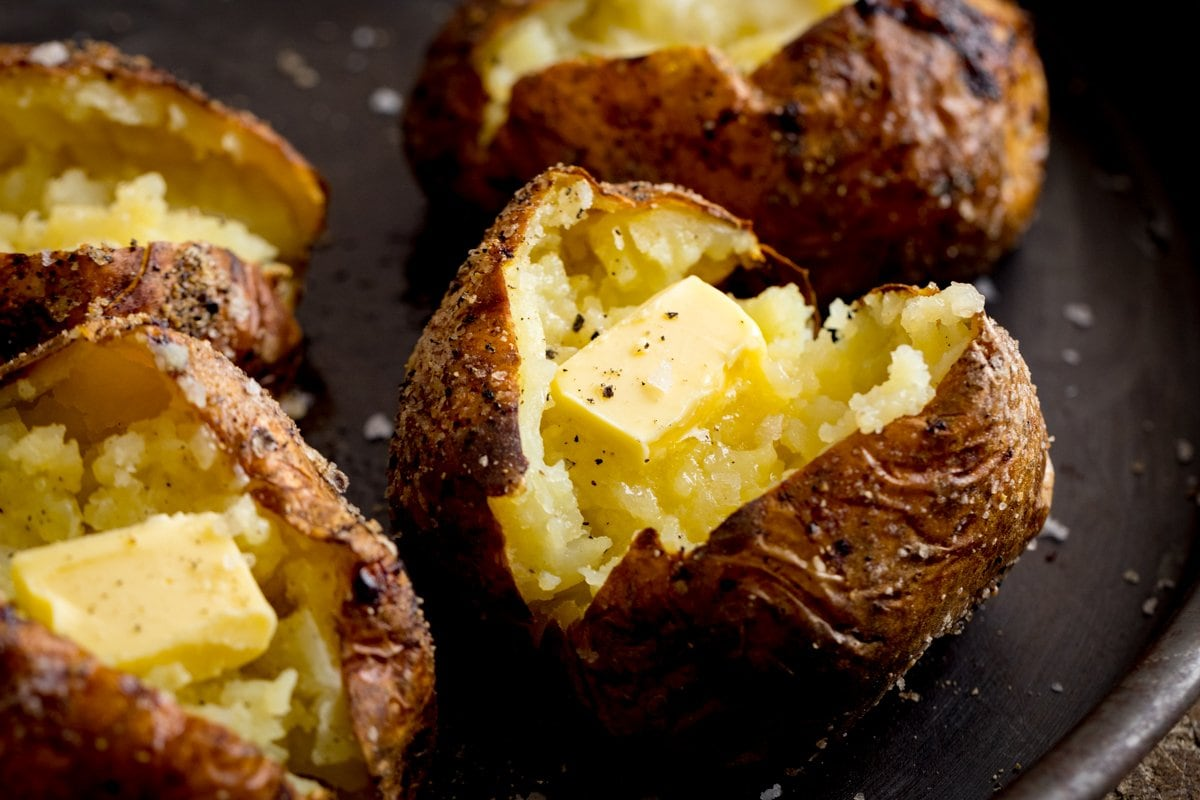 Wide image of an open baked potato with a knob of butter. Three further baked potatoes are arranged around the main one.