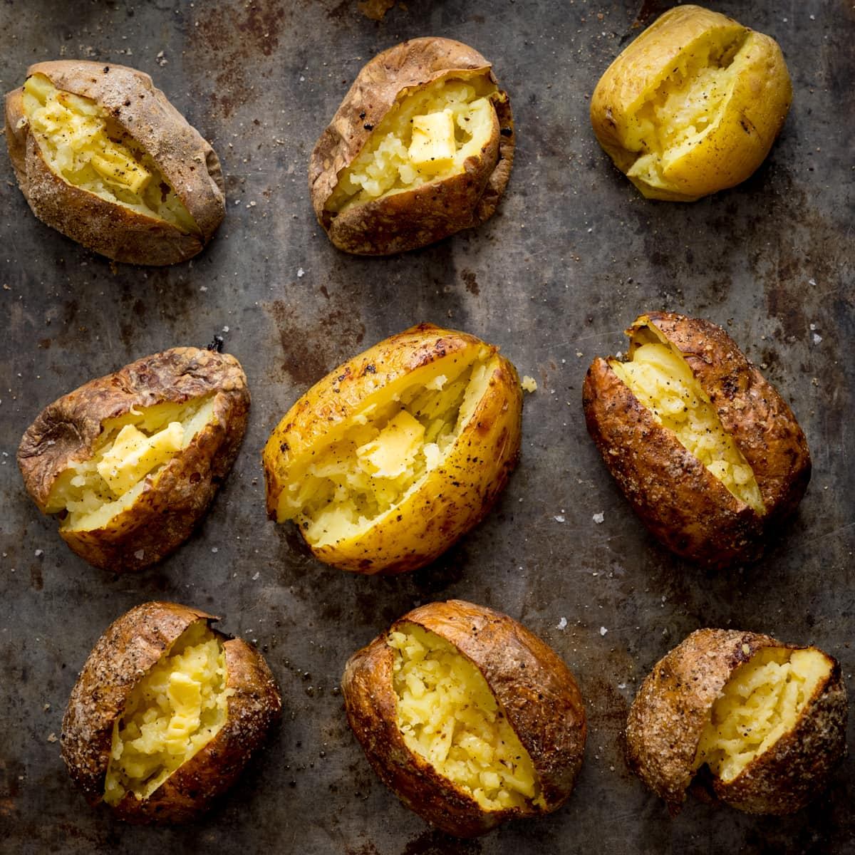Square image showing 9 baked potatoes on a metal tray.