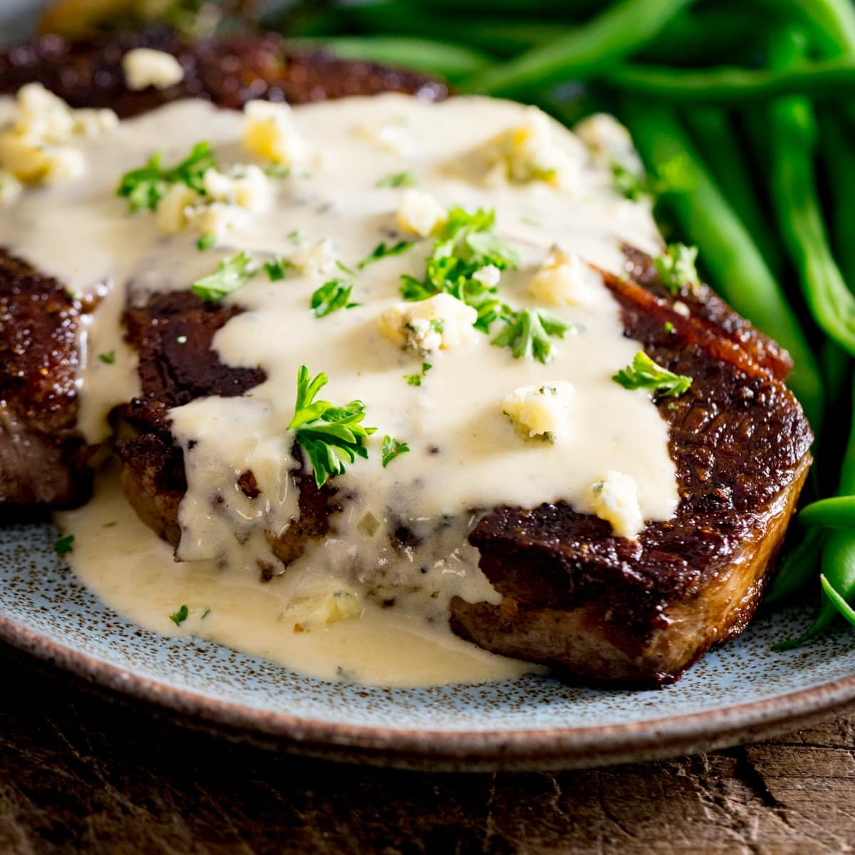 A cooked steak with blue cheese sauce over the top with some green beans, served on a blue plate