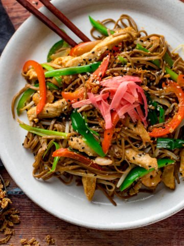 a square image of chicken yakisoba on a white plate with some chopsticks on the side, placed on a wooden board with some ingredients in the background