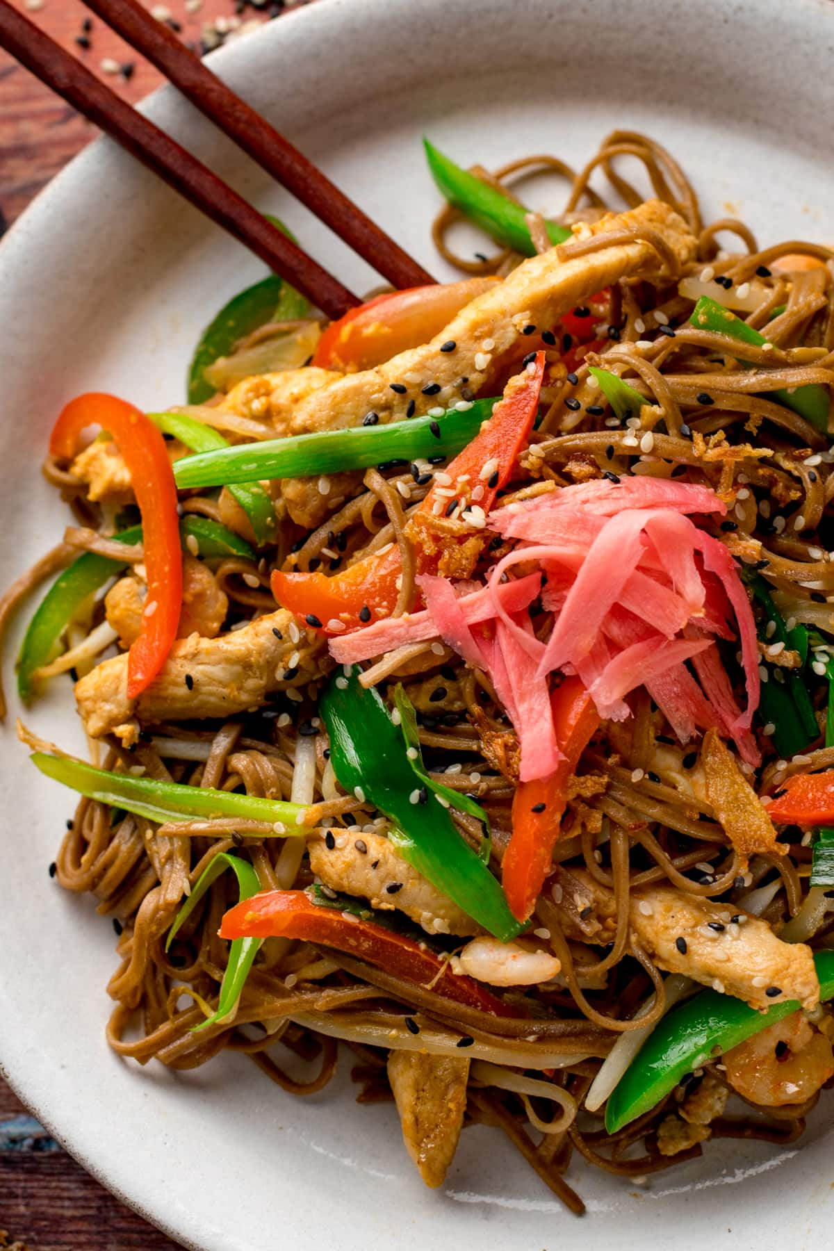 Close up of chicken yakisoba on a white plate with some chopsticks on the side
