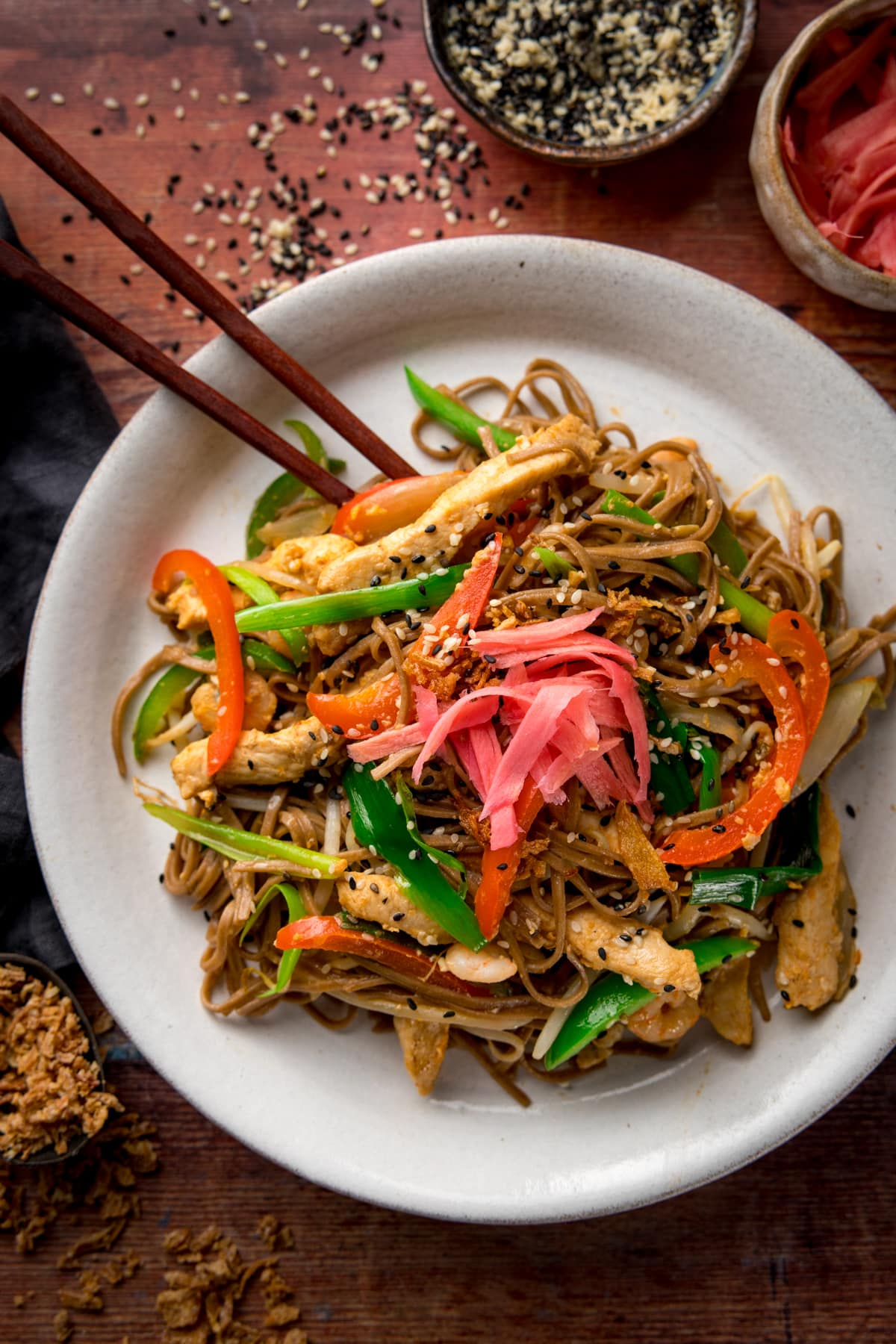 A tall image of chicken yakisoba on a white plate with some chopsticks, on a wooden board