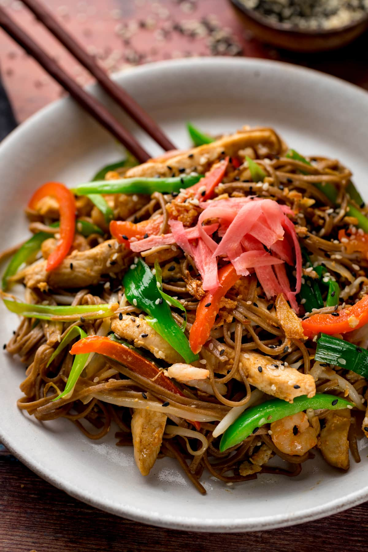 A close up of chicken yakisoba with some chopsticks on a white plate