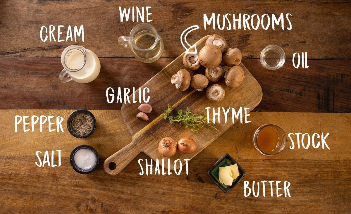 A wooden table with butter, mushrooms, thyme, shallots, garlic, wine, cream and salt and pepper on a wooden board