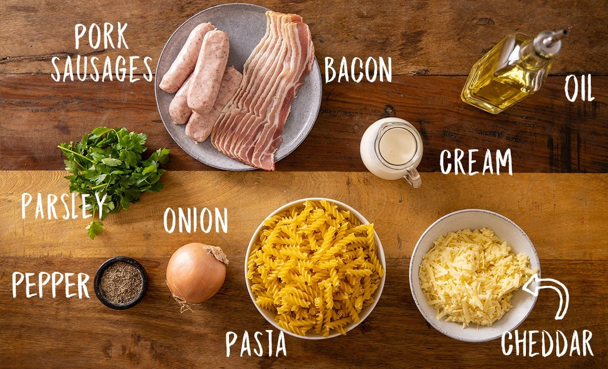 Ingredients for creamy sausage pasta recipe on a wooden table.