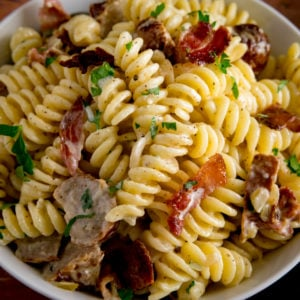 Overhead image of creamy pasta with sausage and bacon in a white bowl.