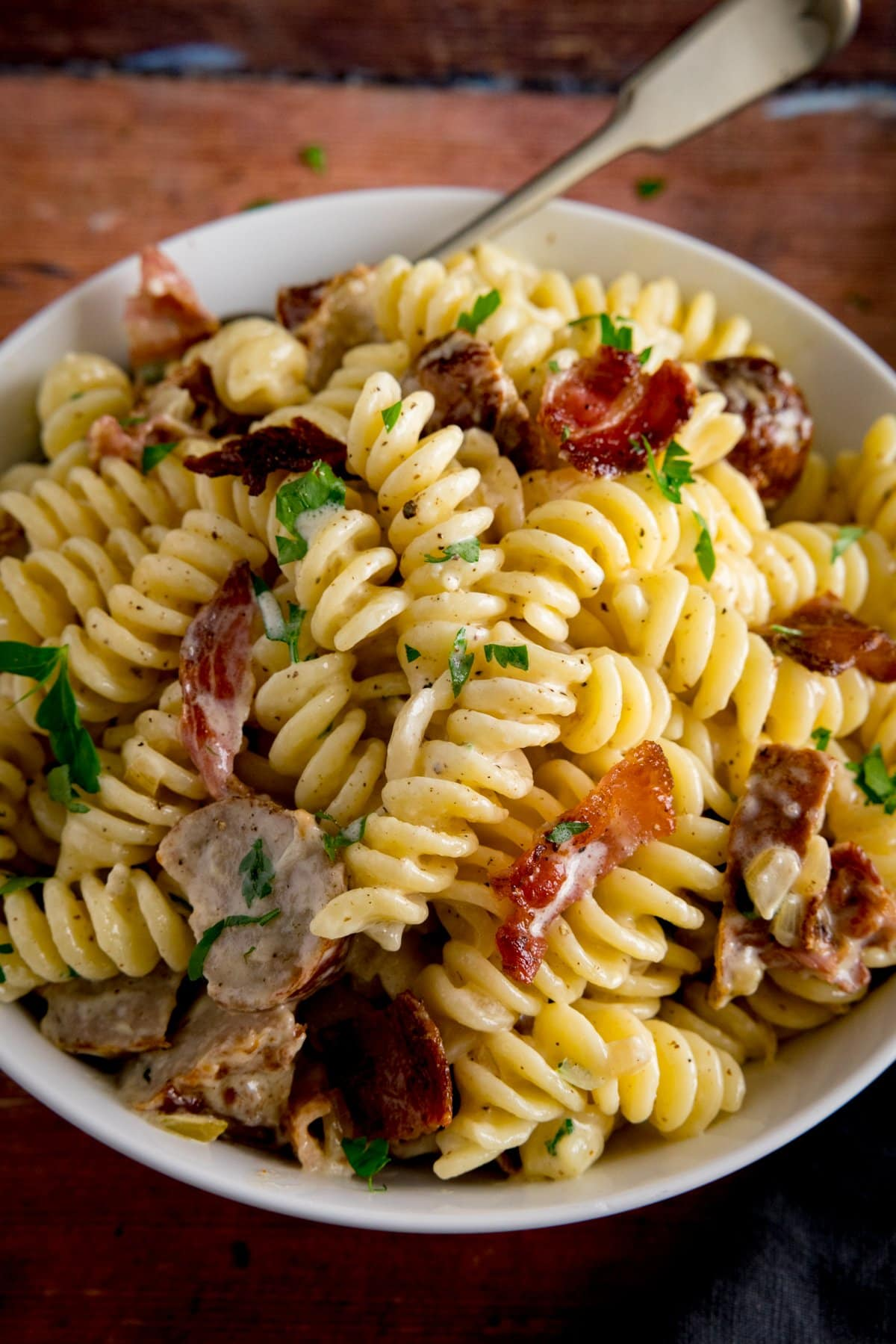 creamy pasta with sausage and bacon in a white bowl on a wooden surface. There is a fork sticking out of the pasta.