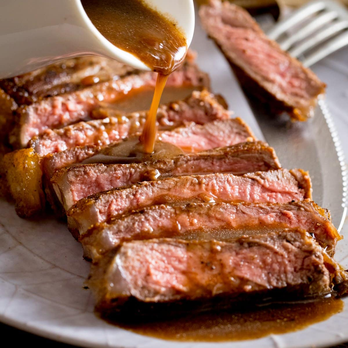 Sliced and cooked steak with red wine jus being poured over the top from a white jug, a fork with steak on it is on the side of the plate