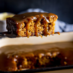 Square image of a piece of sticky toffee pudding being lifted from a baking tin