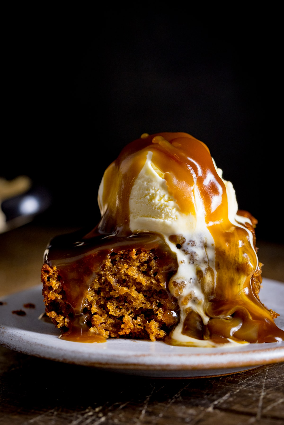 A piece of sticky toffee pudding on a white plate, topped with ice cream and toffee sauce against a dark background.
