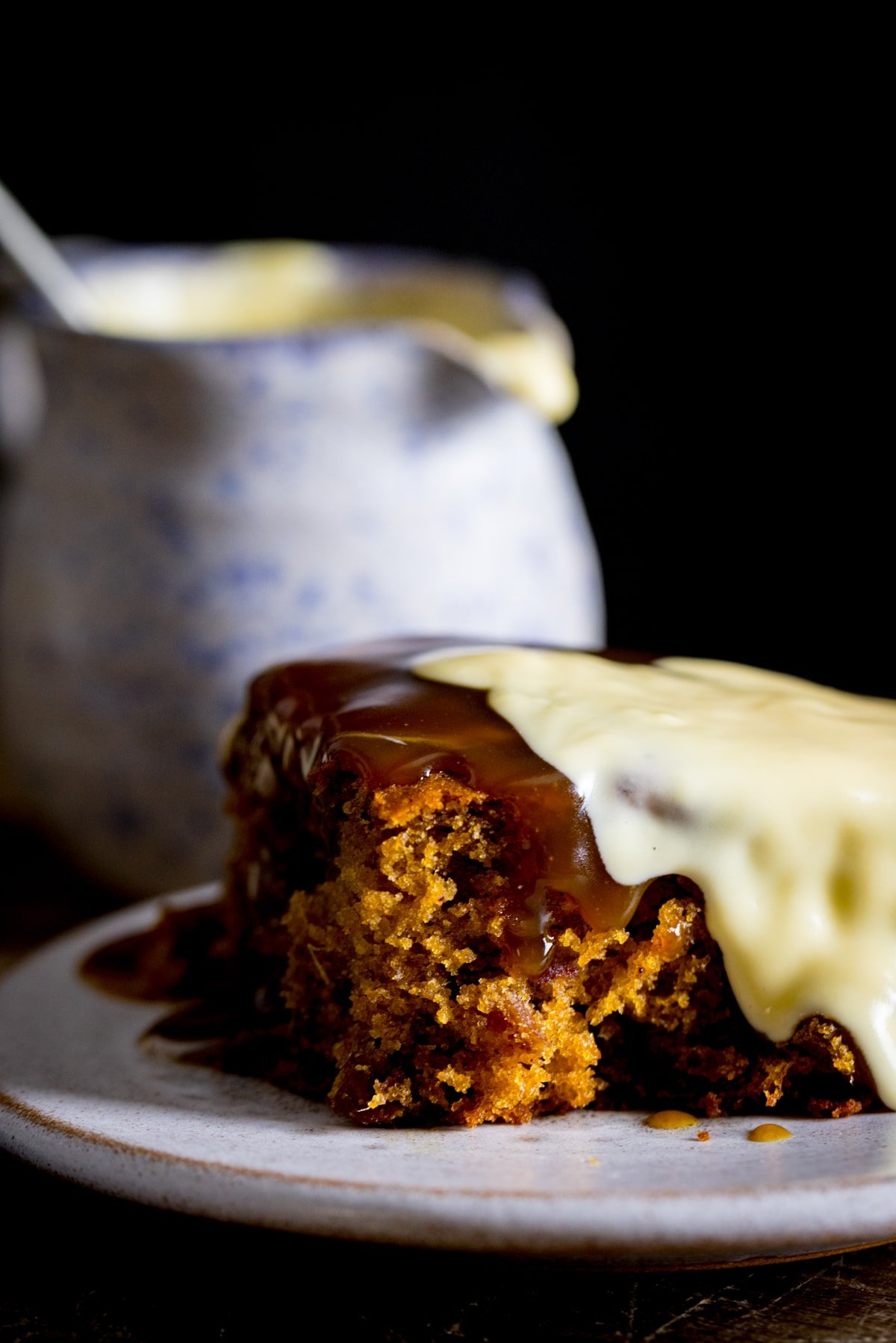 Piece of sticky toffee pudding on a plate, topped with custard. Jug of custard in the background.