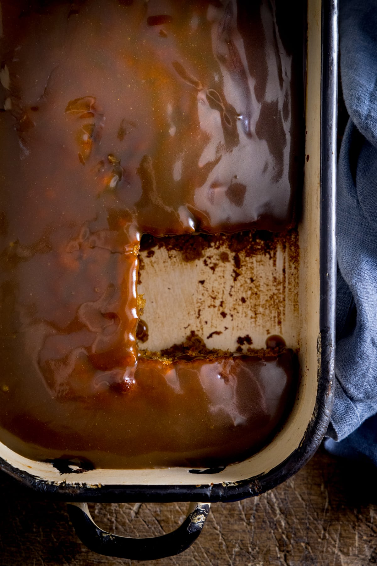 Overhead of sticky toffee pudding with a piece taken out.