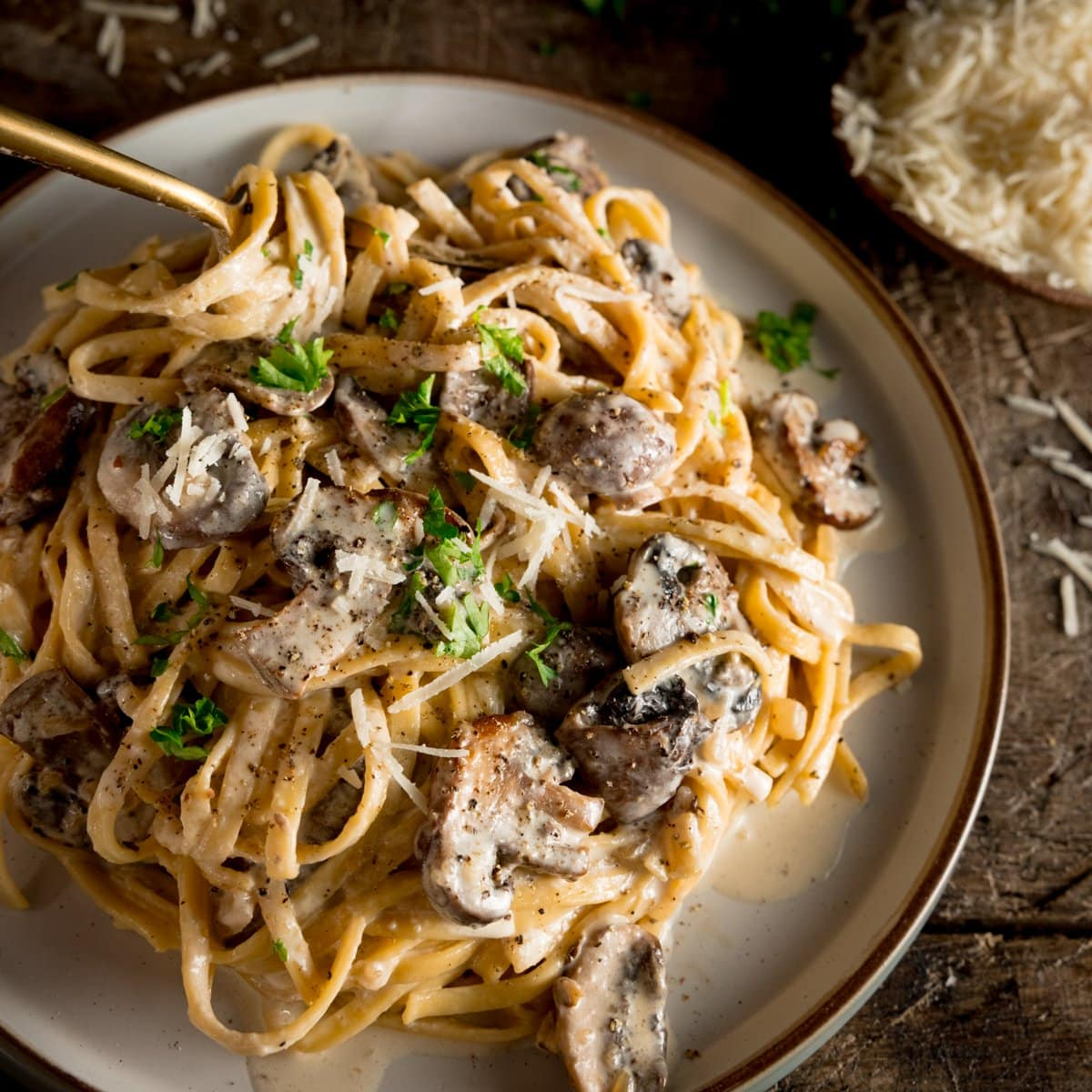 a square shot of creamy mushroom pasta on a white plate with a spoon dug in, on a wooden board with some parmesan in the background